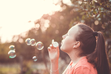 Pretty young brunette woman making soap bubbles during lovely summer sunset (warm filter, color toned image)