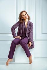 Tense thoughtful barefoot woman sitting coub, wearing purple suit.