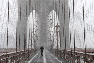 A pedestrian walks through blinding snow across the Brooklyn Bridge during Storm Grayson in New York City