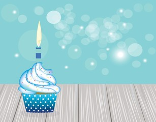 Cupcake with blue candle on blue blurred background, birthday card for boys