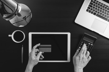 Internet shopping concept.Top view of hands working with laptop and credit card and tablet computer on dark wooden table background,black and white