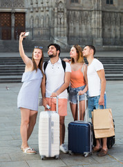 happy adult tourists taking selfie on camera in smartphone