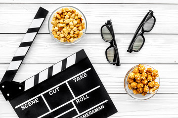 Popcorn, rusks for watching film. Clapperboard and glasses on white wooden background top view