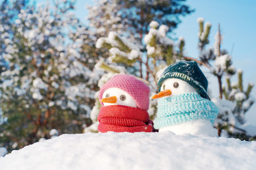 Two small snowmen the girl and the boy in knitted caps and scarfs on snow in the winter. Festive background with a lovely snowman. Christmas card, copy space