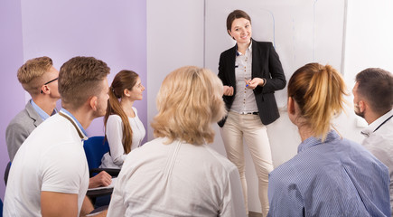 Female teacher lecturing to students at auditorium