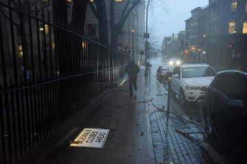 A man runs past tree limbs and debris scattered on the sidewalk as heavy rain and gusting winds from Storm Grayson cause disruptions in Halifax