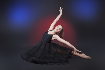 Graceful ballerina in a transparent skirt. Isolated on black background in studio color light