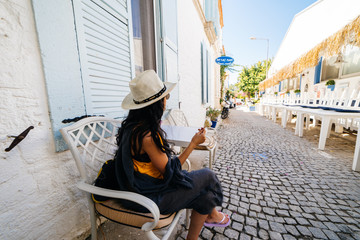 Woman tourist in hat sitting on the europe street,greece