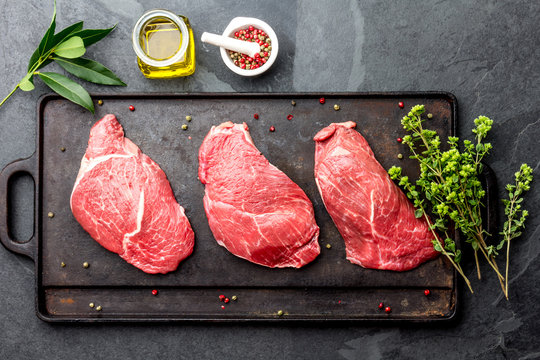 Raw beef steaks with herbs and spices on cast iron frying board, top view