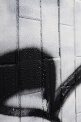 A fragment of a graffiti pattern, applied to a wall of cold tiles, which is covered with a fine condensate. The concept of street art in inappropriate weather