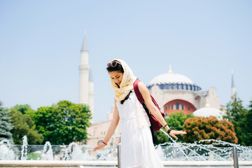 Young woman in a scarf with a backpack on the background of Aya Sofia and a fountain. Summer vacation, traveler, Turkey