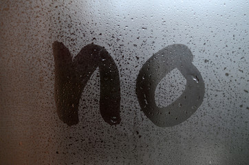 "The English word ""No"" is written with a finger on the surface of the misted glass"