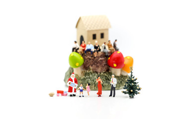Miniature people with happy family holding balloons in front of wooden house as property or mortgage concept.
