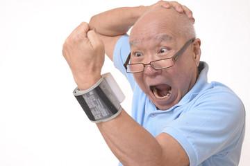 血圧を測定し驚くシニア