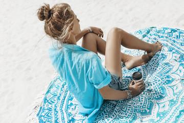 beautiful young cheerful woman in bikini sitting on the beach with cup of coffee