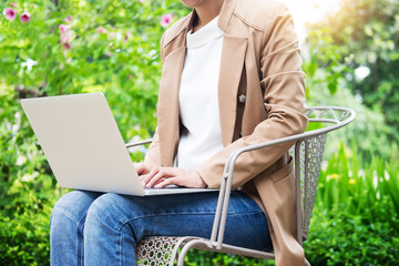business woman hand using laptop on table in garden.