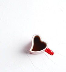 Cup of tea in shape of heart on white background