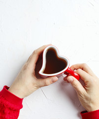 Female hand holding cup of tea in shape of heart on white background, top view