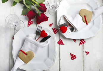 Festive table setting for Valentine's Day with cutlery and gift boxes on white wooden table