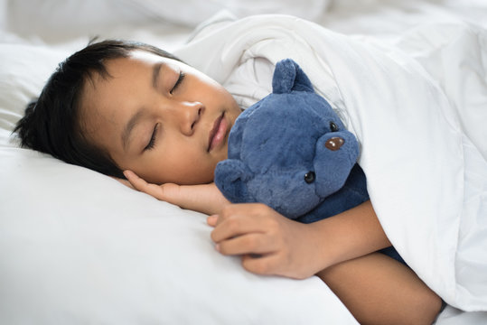 boy sleeping on bed with teddy bear white pillow and sheets.boy fall asleep in morning.sleep concept