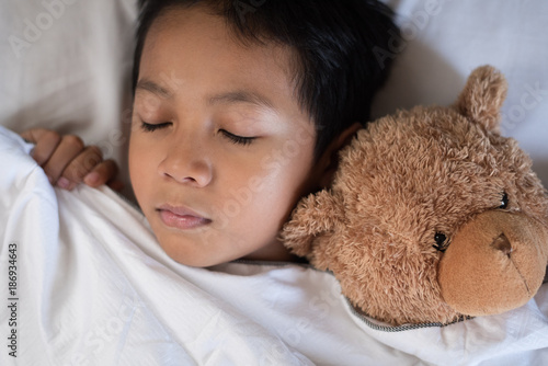 9a07fa36b boy sleeping on bed with teddy bear white pillow and sheets.boy fall asleep  in