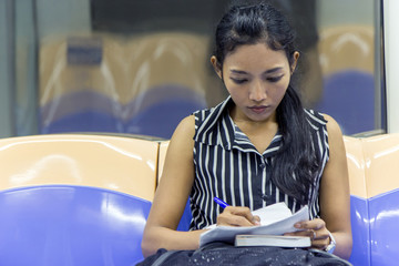 Asian tourist viewing the documents on the subway. Woman writes on a paper while riding the metro. Girl goes by train and studying her notes.