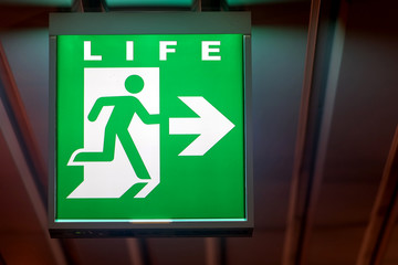 The emergency exit sign shows the direction of Life. The emergency exit board hangs on the ceiling of the building.
