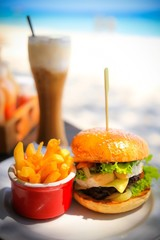 Shallow depth of field of Burger set with ice coffee on the beach.