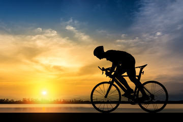 Silhouette of man ride a bicycle in sunset background Wall mural