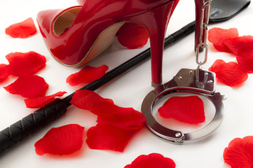 Kinky sex and BDSM games concept with a pair of red and shiny high heel stilettos, a leather crop under the shoes, a pair of metal handcuffs and rose petals surrounding the scene