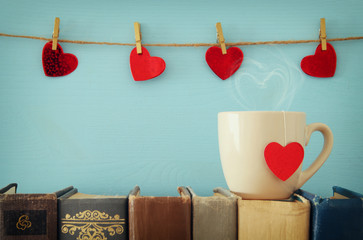 Valentine's day background. Cup of coffee or tea or coffee over old books.