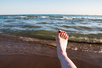 Female feet and sea wave on a summer
