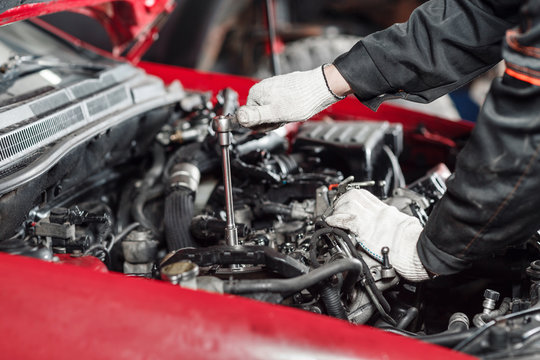 Repairing of modern diesel engine, workers hands and tool. Close-up of an auto mechanic working on a car motor