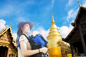 Wall Mural - Young Asian woman backpacker is enjoy traveling in Wat Phra Singh in Chiangmai, Thailand.