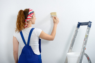 pretty young woman painting the wall