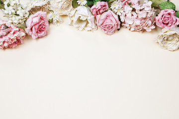 Frame made of pink and beige roses, green leaves, branches on beige background. Flat lay, top view. Wedding's background with copy space.