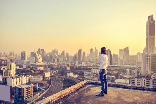 Western businessman looking at the city at sunset
