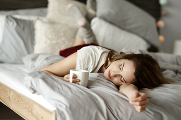 Woman with coffee reclining in bed