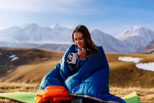 smiling young girl sitting in a blue sleeping bag drinking hot tea on the background of the Caucasian mountains