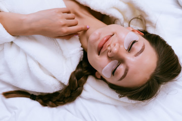 smiling happy girl lies in bed, under eyes white patches, eyes closed