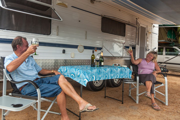 Retired couple sitting under awning of a large caravan toasting retirement.