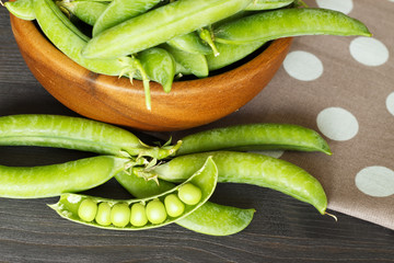 Pods of peas in a wooden bowl. Country style. The concept of healthy eating.