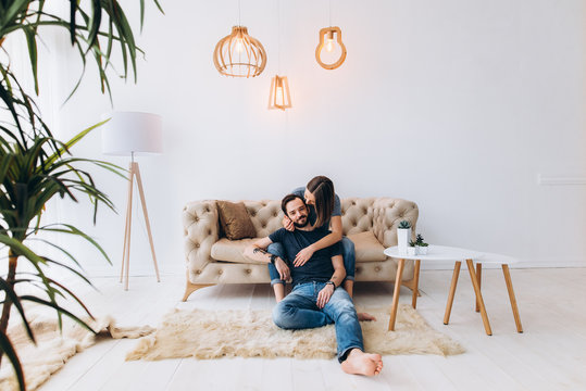 Love story. Beautiful couple sit on sofa, in a large, light interior room. Family, love, tenderness. Side view
