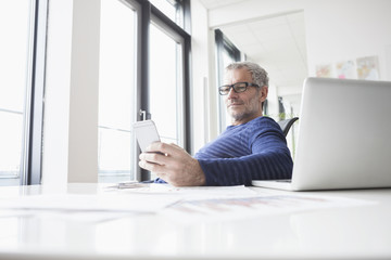 Mature man sitting in office with laptop, using smart phone