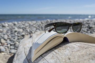Sunglasses on opened book on pebble beach, close-up