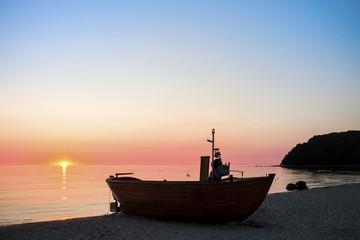 Germany, Ruegen, Binz, Beach with fishing boat at sunset