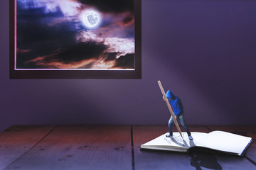 tiny man writing heart on book among light of full moon