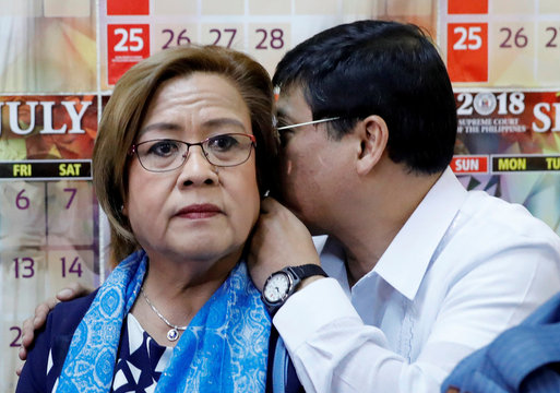 A lawyer whispers to detained senator De Lima before the start of a court hearing in Quezon City