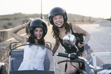 Two women on sidecar posing and smiling.Jaen, Spain
