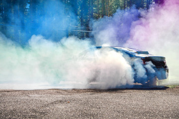 Drift car warming up the tires before  start, waiting for race to begin. Blue and purple smoke all around